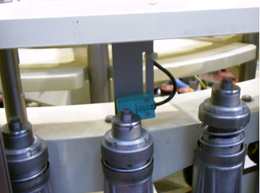 Container Presence sensor, installed by our staff in a Krones™ AG Labeller Machine.  In the specific case, it is sensible to the upper position of the metal bell when a bottle lies between a tulip and a rotary plate.  All Container or Bottle Presence sensors, whatever their technology, are part of the important family of the Triggers