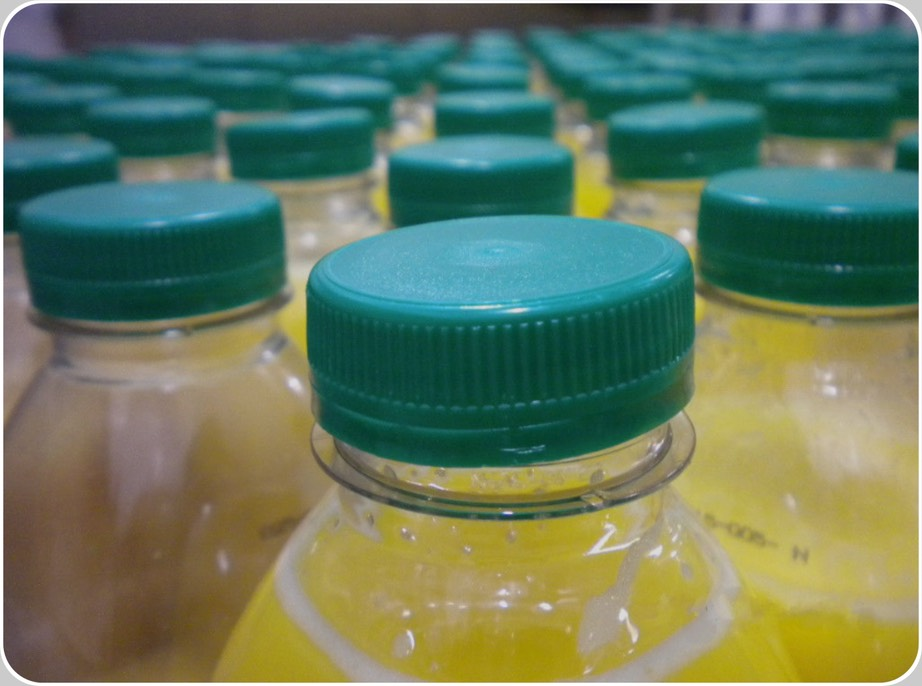 Aseptically filled juice contaminated due to malpositioned cap.     Juice bottles shortly before to be packed. Two of them having their cap visibly malpositioned.  All times the product is part of the most sensitive categories, filled without added preservatives in an aseptic environment, containers' leakages have to be inspected by systems applying multiple-physical principles measurements.  And not only camera-based electromagnetic, like these